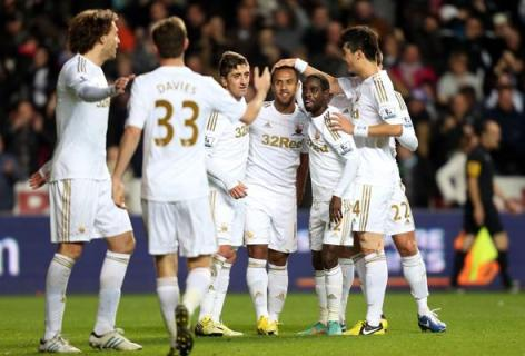 Swan break | Swansea City players congregate after a goal from Wayne Routledge, and may have more to celebrate come February 24. (Image | Talking Baws)