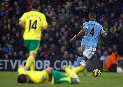 Canary grounded | Combative Kompany escapes with the ball after a robust challenge on Norwich City midfielder Bradley Johnson. (Image | Pink 'Un)